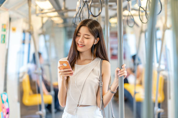 Young Asian woman passenger listening music via smart mobile phone in subway train