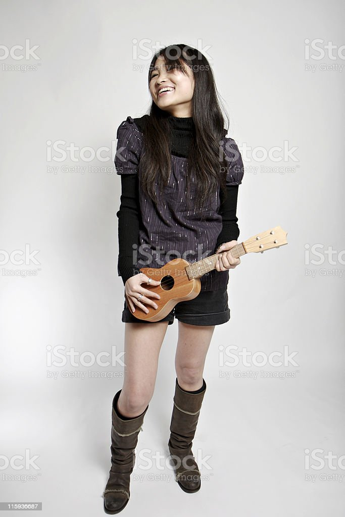 Young Asian (Japanese) woman playing a tiny guitar A young Japanese woman is playing a ukulele as though it was a miniature rock and roll guitar. Adult Stock Photo