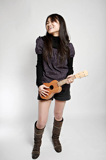 Young Asian (Japanese) woman playing a tiny guitar stock photo