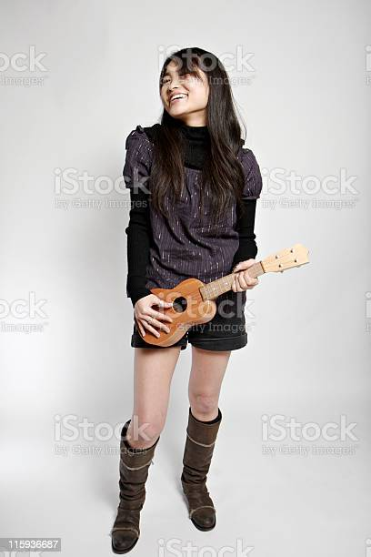Young Asian Woman Playing A Tiny Guitar Stock Photo - Download Image Now