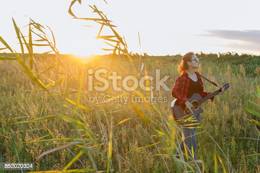young asian woman playing guitar in field against sunbeam.