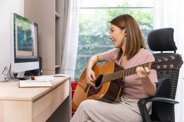 Young Asian woman playing guitar live-streaming on social media stock photo