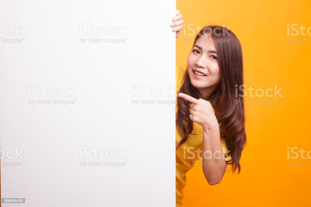 Young Asian woman point to a  blank sign in yellow dress stock photo