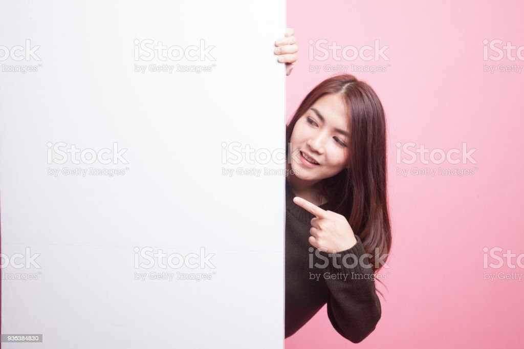 Young Asian woman point to a  blank sign. stock photo