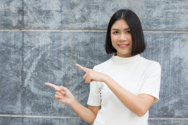 Junge Asiatin Punkt, Leerzeichen am Zement Hintergrund. Frau mit Bildungskonzept. – Foto