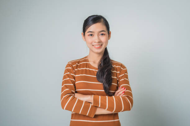 Young asian woman portrait smiling with crossed arms, happy feeling in brown sweater. stock photo