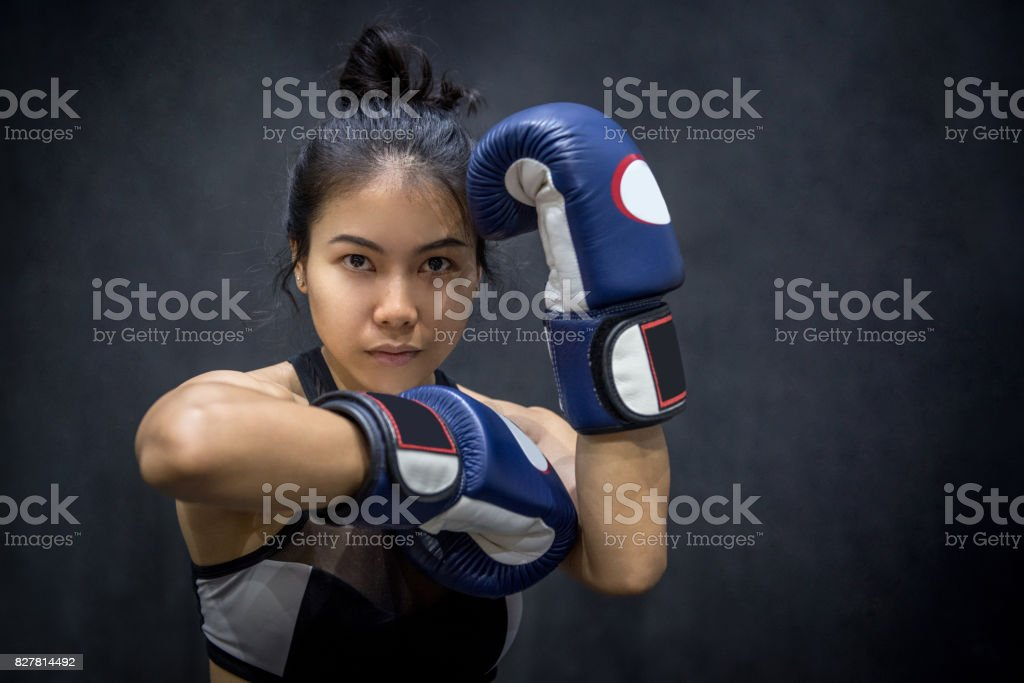 young Asian woman posing with blue boxing gloves stock photo