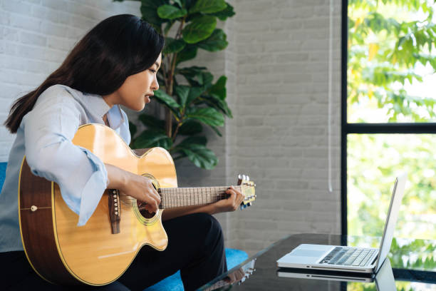Young Asian woman practicing and learning how to play guitar on laptop computer monitor. Female guitarist watching online tutorial stock photo