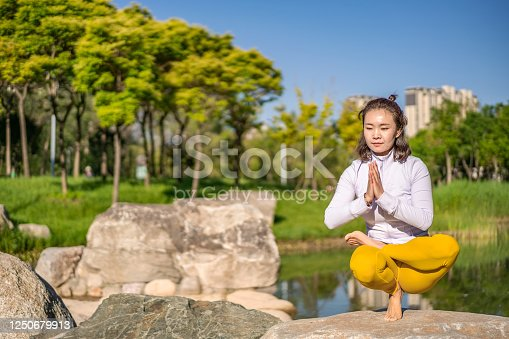 Young Asian woman practicing yoga in city public park