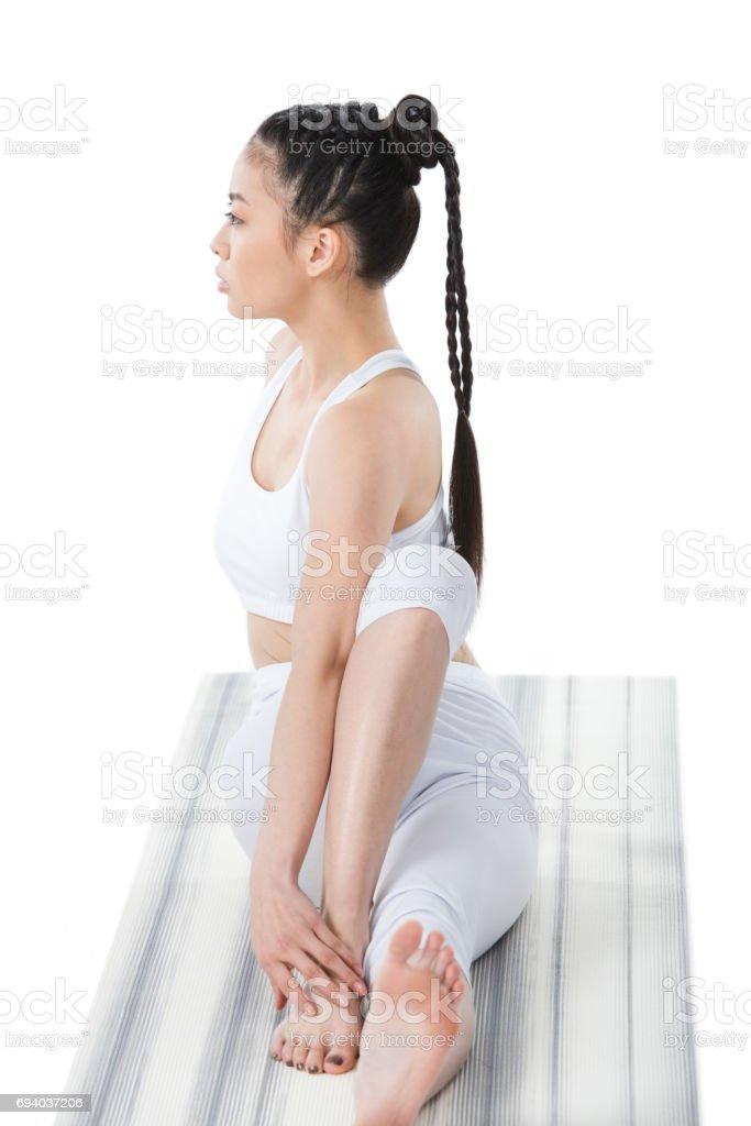 young asian woman practicing yoga in twisting sage pose (Marichyasana) on yoga mat stock photo