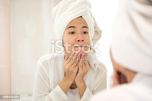 A portrait of a Young asian woman preesing her face, trying remove acne