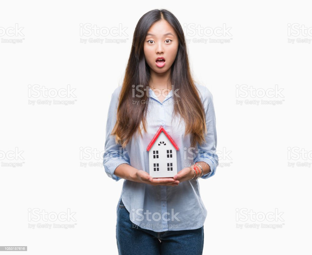 Young asian woman real state agent holding house isolated background...