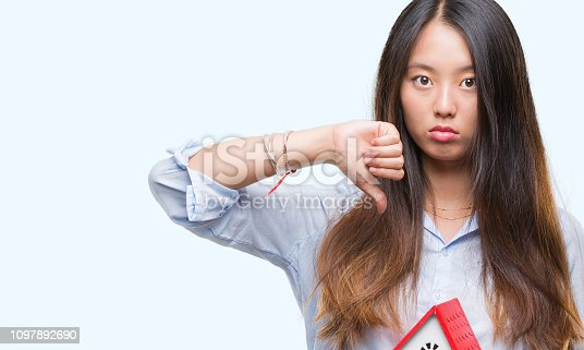Young asian woman real state agent holding house isolated background with angry face, negative sign showing dislike with thumbs down, rejection concept