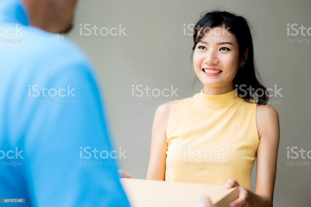 Young Asian Woman receive Pizza Box from  Delivery Man with Attractive Smiling at Home. People with Delivery Concept. stock photo