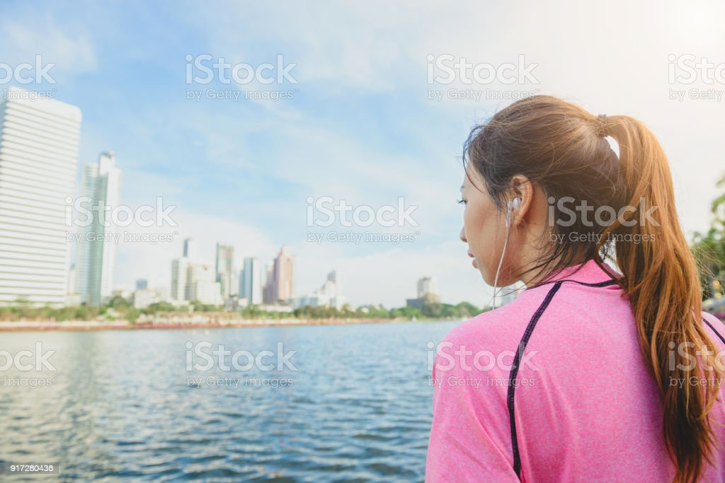 Young asian woman relax herself by listening to music after city running exercise with a city view background and warm light cleared sky late of the afternoon. Outdoor running exercise concept. stock photo