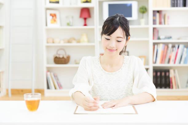 若いアジア女性のリビング ルームでリラックス - 書く ストックフォトと画像