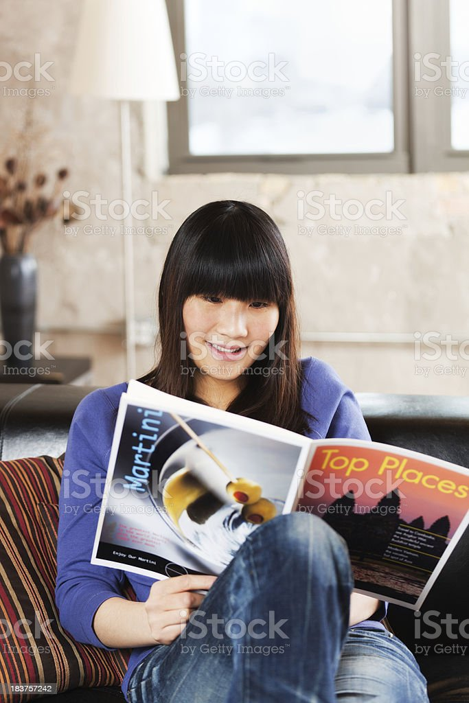 Young Asian Woman Relaxing, Reading Magazine in Loft Condominium Home royalty-free stock photo