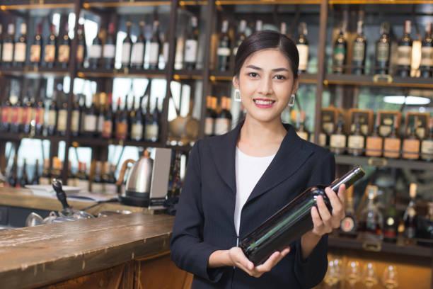 Junge asiatische Frau Restaurant Catering Service glücklich Emotion. Frau anwesend Rotwein für Kunden in Bar. Frau mit Wein in der Bar-Konzept. – Foto