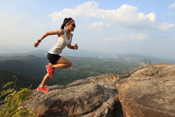 Young asian woman runner running on mountain peak stock photo