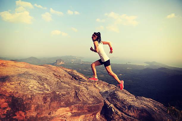 jóvenes asia mujer corredor corriendo en el pico de la montaña - trail running fotografías e imágenes de stock