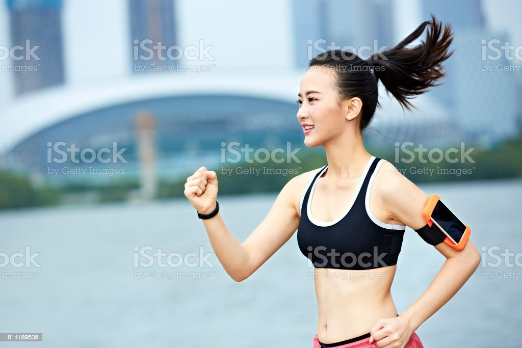 young asian woman running outdoors stock photo