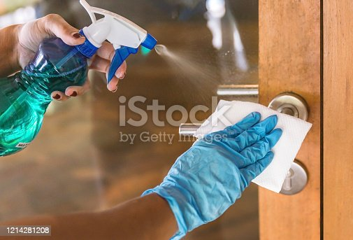 Close up shot Asian woman cleaning door handle with disinfectant spray and wet wipe, for Coronavirus precautions