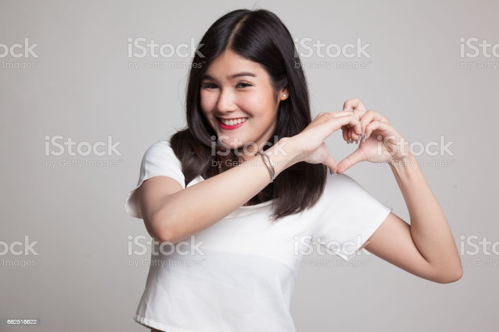 Young Asian woman show heart hand sign. royalty-free stock photo