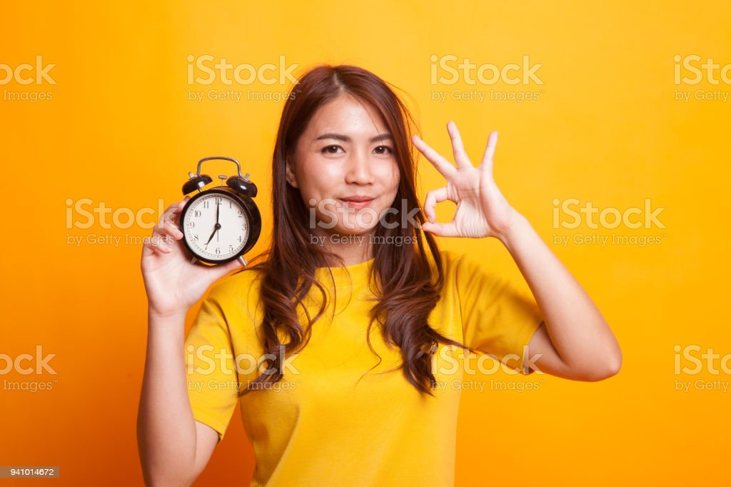 Young Asian woman show OK with a clock in yellow dress stock photo