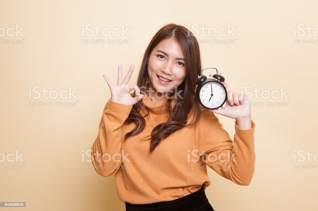 Young Asian woman show OK with a clock. stock photo