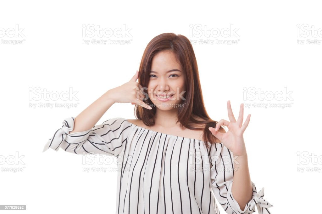 Young Asian woman show with phone gesture and OK sign. royalty-free stock photo