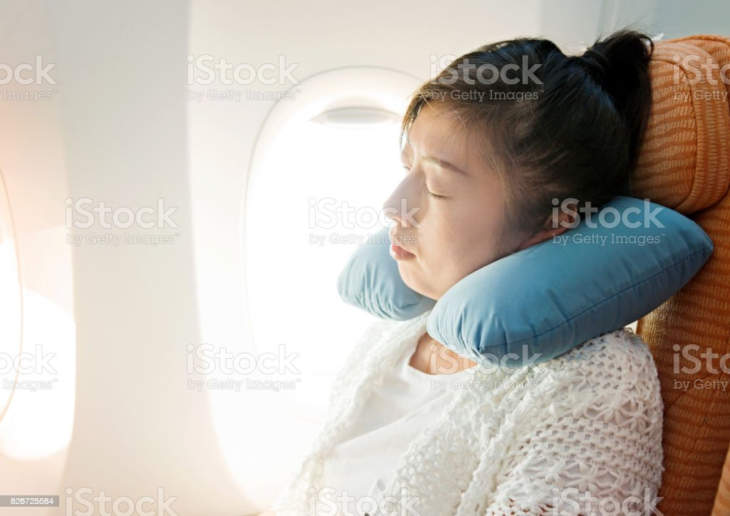 Young asian woman sleeping on airplane stock photo