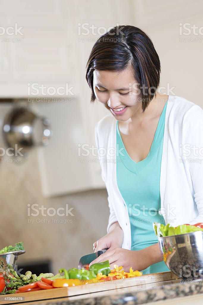 Young Asian woman slicing fresh vegetables for recipe royalty-free stock photo