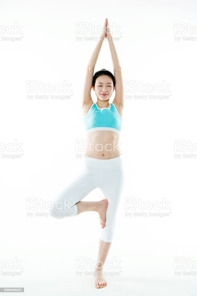Young asian woman standing in yoga tree posture stock photo