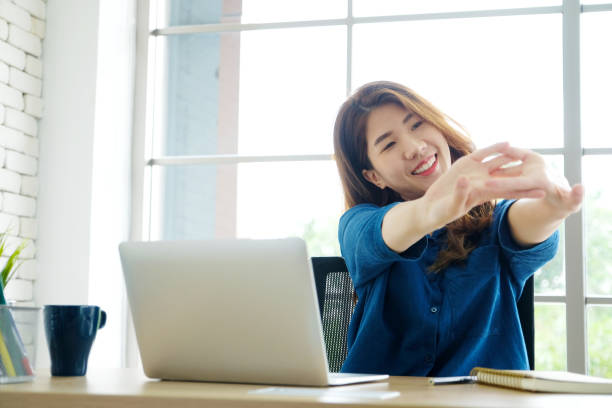 Young asian woman stretching body for relaxing while working with laptop computer at her desk, office lifestyle, business situation stock photo
