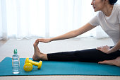 istock Young asian woman stretching on a yoga mat 1313803636