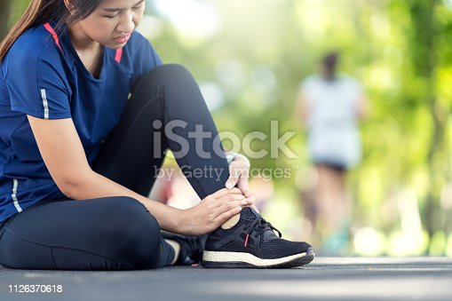 istock Young asian woman suffering ankle injury. Runner girl is injured by sprain ankle while running or exercising. Female runner touching foot in pain due to sprained ankle. Injury from workout concept 1126370618