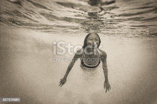 Serene image of a young Asian woman swimming alone underwater.