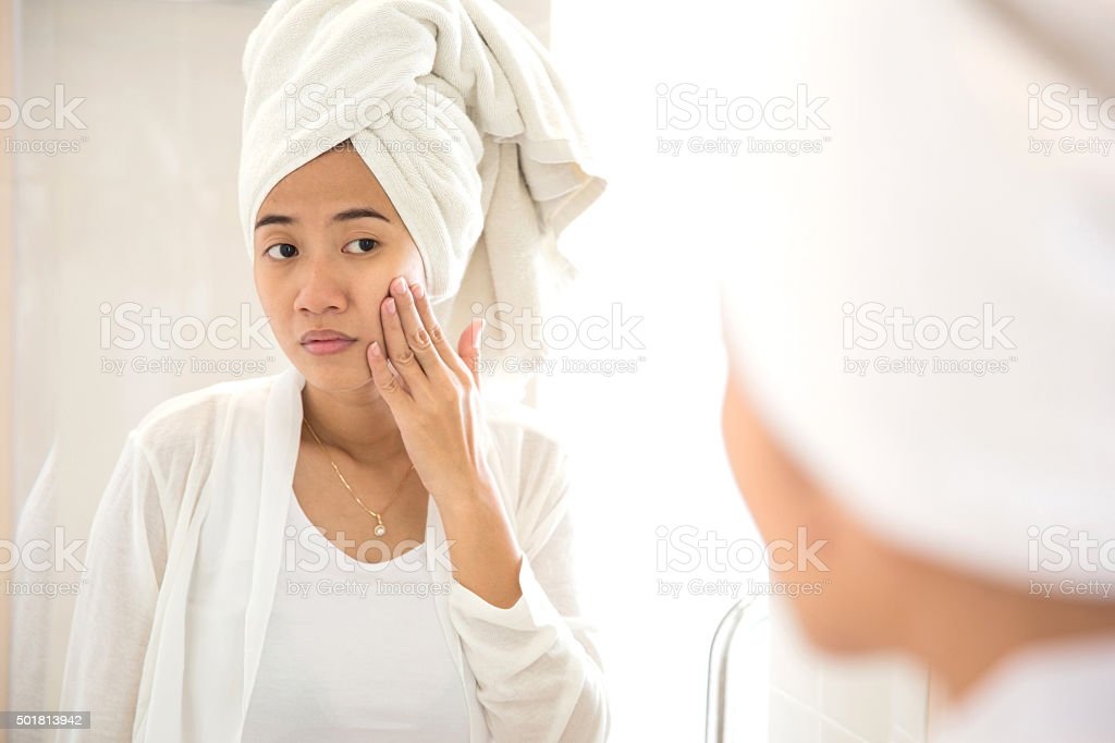 Young Asian woman taking care of her face stock photo