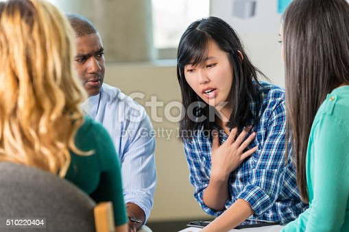istock Young Asian woman talks in support group 510220404