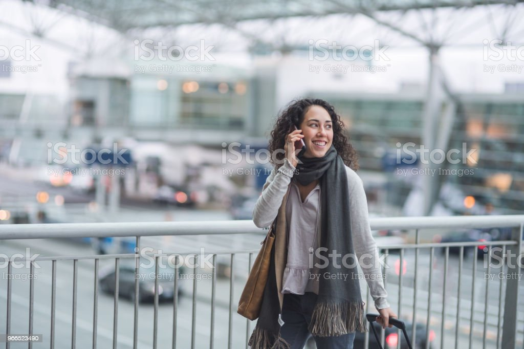 A young ethnic woman traveling solo pulls her suitcase through the...