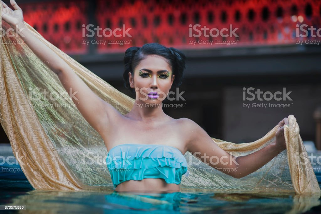 Young Asian Woman Tanned Skin And Black Shine Hair in blue gold...