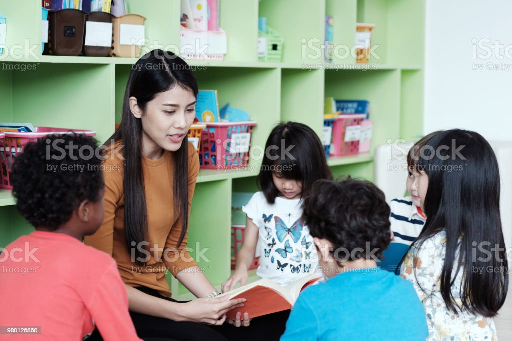 Young asian woman teacher teaching kids in kindergarten classroom,  preschool education concept - Stock image .