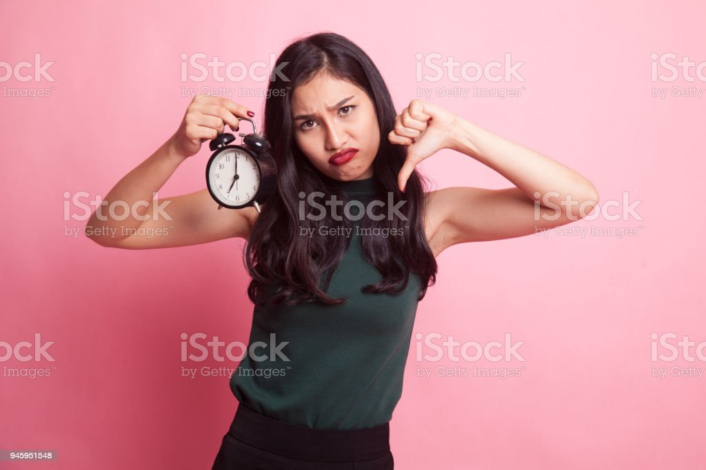 Young Asian woman thumbs down with a clock. stock photo