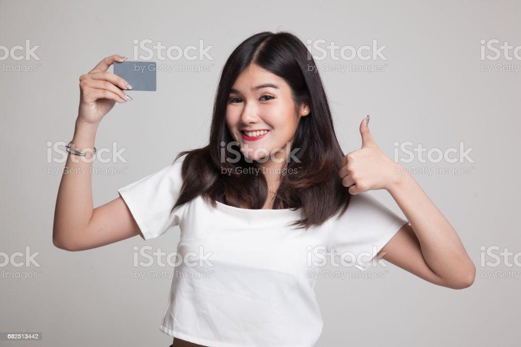 Junge Asiatin Daumen nach oben, mit einer leeren Karte. Lizenzfreies stock-foto