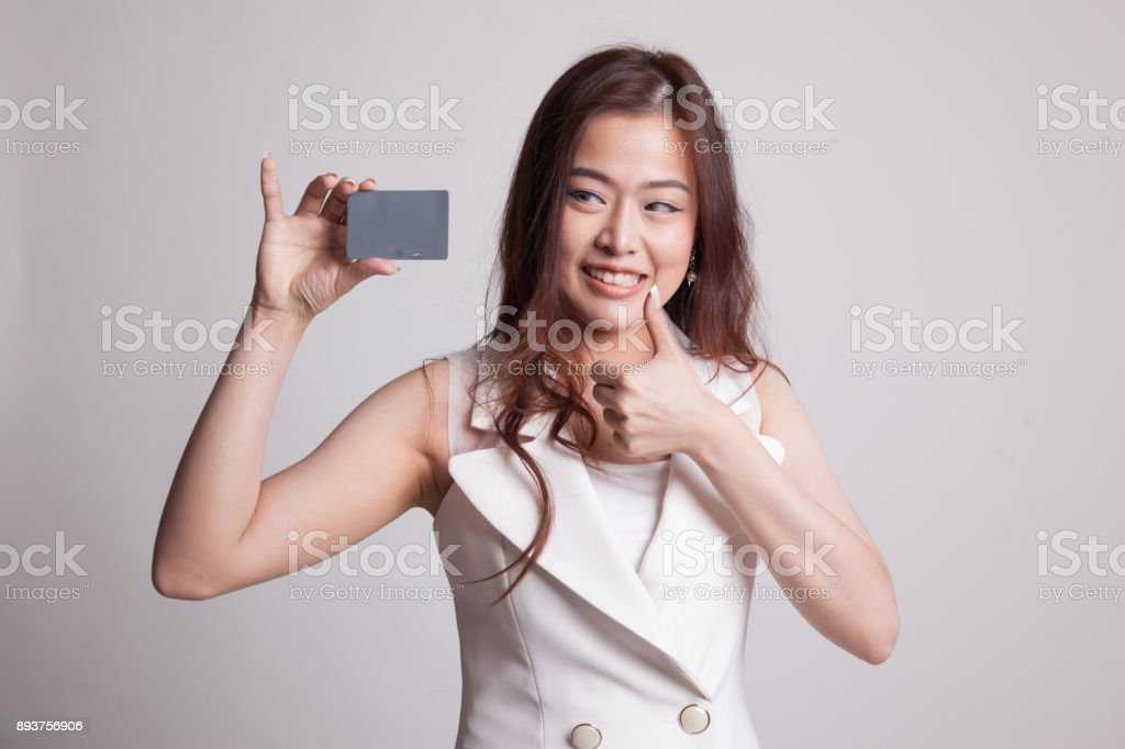 Young Asian woman thumbs up with a blank card. stock photo