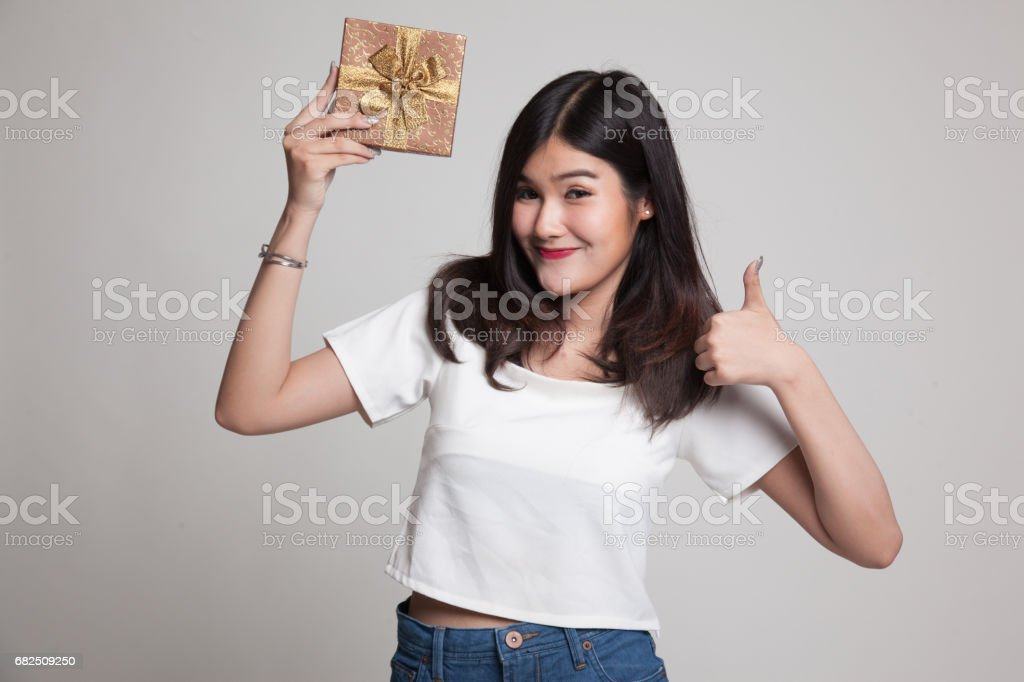 Young Asian woman thumbs up with a gift box. royalty-free stock photo