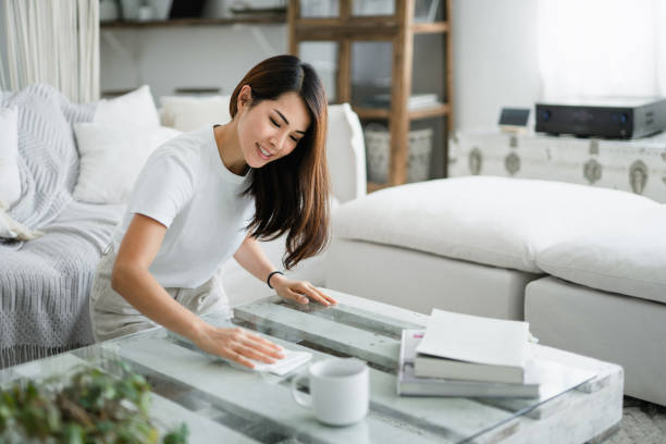 Young Asian woman tidying up the living room and wiping the coffee table surface with a cloth