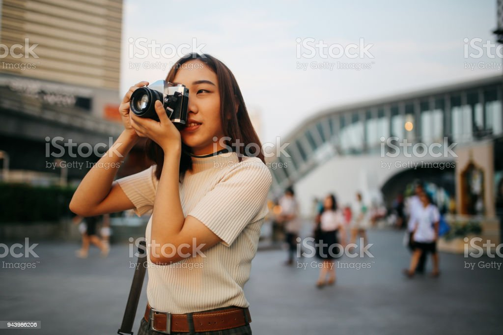 Young Asian woman traveler in Bangkok downtown district, holding a vintage film camera Vintage colored portrait of a young Asian woman traveler, relaxing at the busy Siam station of the Skytrain, next to popular shopping malls and restaurants. She is wearing casual clothing, taking photos with her beautiful analog film camera with a fixed, large aperture, prime lens. Adult Stock Photo
