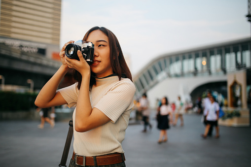 Young Asian Woman Traveler In Bangkok Downtown District Holding A Vintage Film Camera Stock Photo - Download Image Now