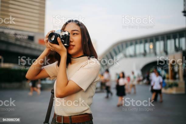 Viajero Mujer Asiática Joven En El Distrito Centro De La Ciudad De Bangkok Con Una Cámara De Película Vintage Foto de stock y más banco de imágenes de A la moda